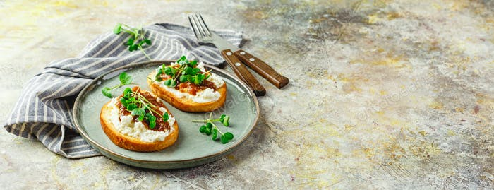 Canape or crostini with toasted baguette, cottage cheese, fig jam