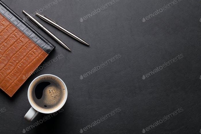 Büro-Leder-Schreibtischtisch mit Notizblock und Kaffee