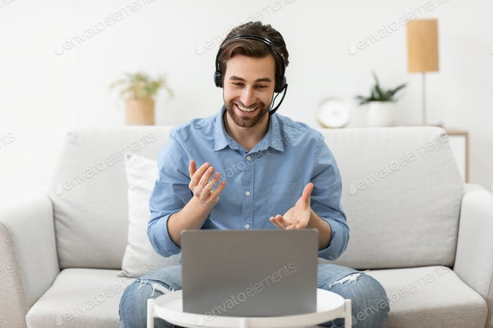 Businessman At Laptop Watching Educational Business Webinar Wearing Headset Indoors