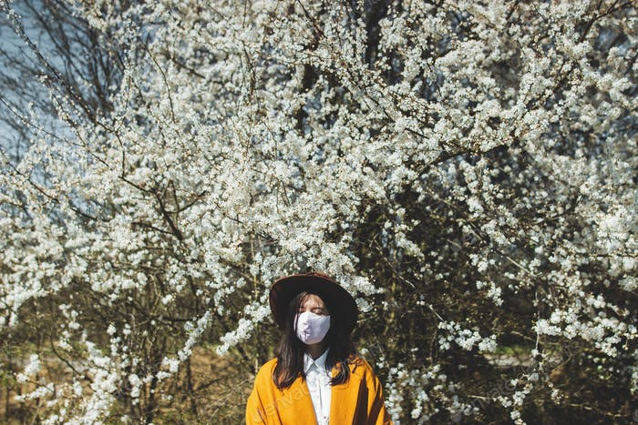 Young beautiful woman wearing face mask in spring park and enjoying blooming cherry trees