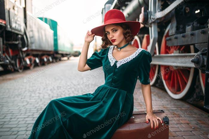 Frau im roten Hut gegen Vintage-Dampfzug