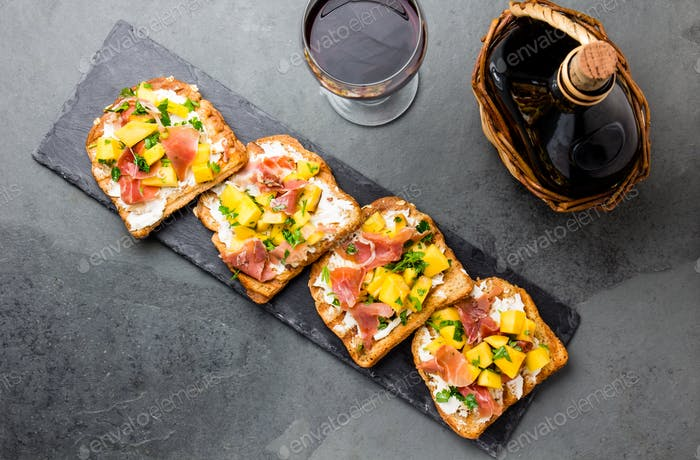 Toasts with cream cheese, ham jamon serrano and mango served on wooden board