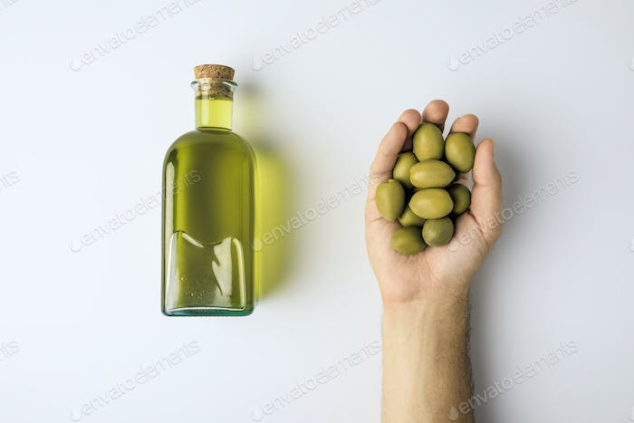 Cropped image of man holding green olives in hand and bottle of olive oil isolated on white