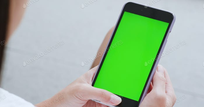 Woman use of cellphone with green screen, chroma key