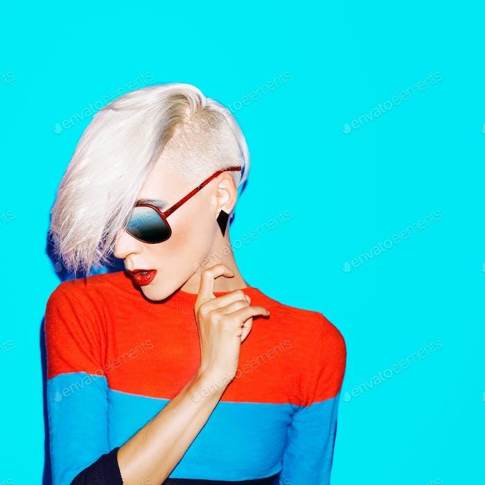Mode blonde Frau mit trendigen Frisur und Sonnenbrille auf einem bl