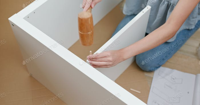 Woman assembling a shelf at home