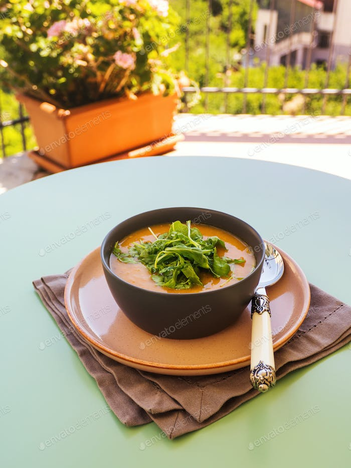 Creamy pumpkin soup served in bowl with arugula