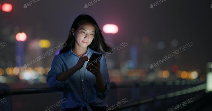 Женщина пользуется мобильным телефоном на открытом воздухе