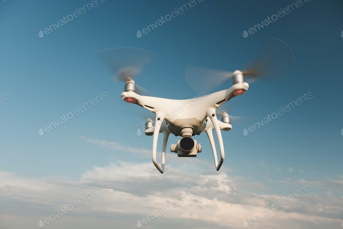 White drone hovering in a bright blue sky
