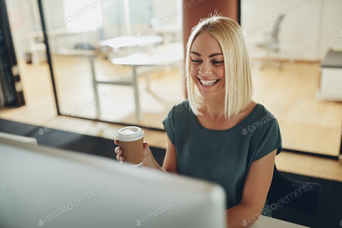 Smiling young businesswoman sitting at her desk drinking a coffee