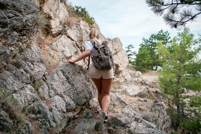 Hiker girl with backpack hiking on trail near rocks