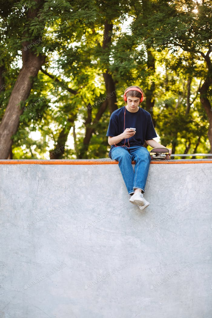 Young cool guy in orange headphones dreamily using cellphone wit