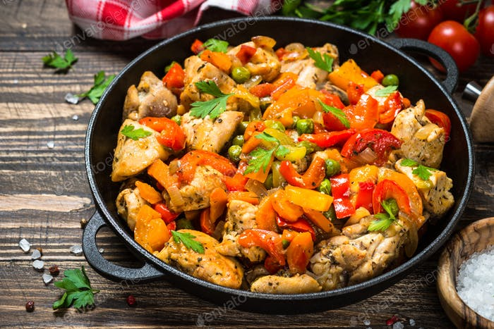 Chicken Stir fry with vegetables on wooden table