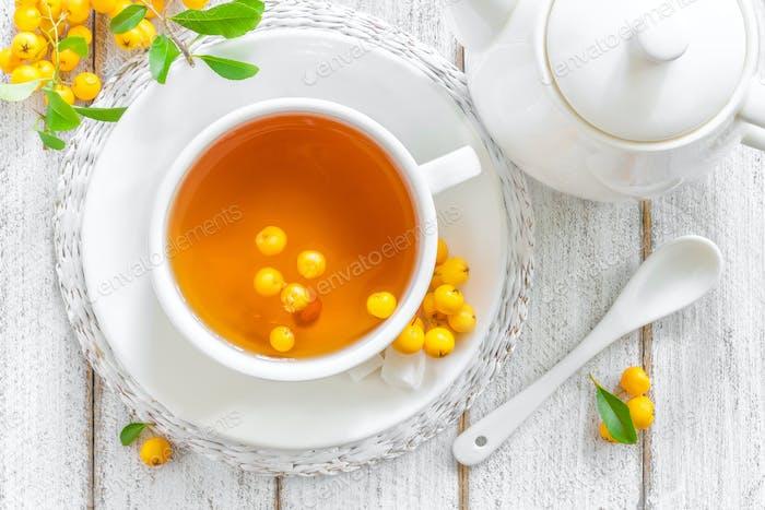 Weißdorntee in einer Tasse mit frischen Beeren auf weißem Holztisch, gesunde Kräuterheilung Heißgetränk