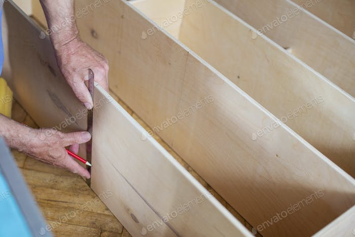 Mature man measuring wooden shelf with ruler while making shelf