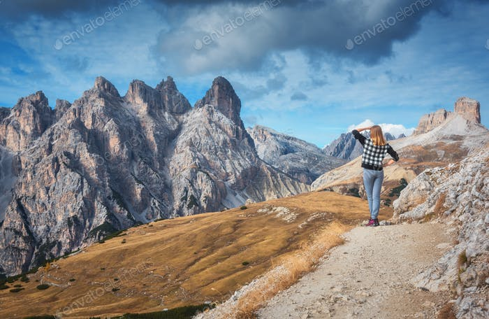 Woman on the trail is looking on majestic mountains at sunset