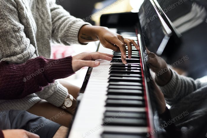 Couple praticing on a piano together