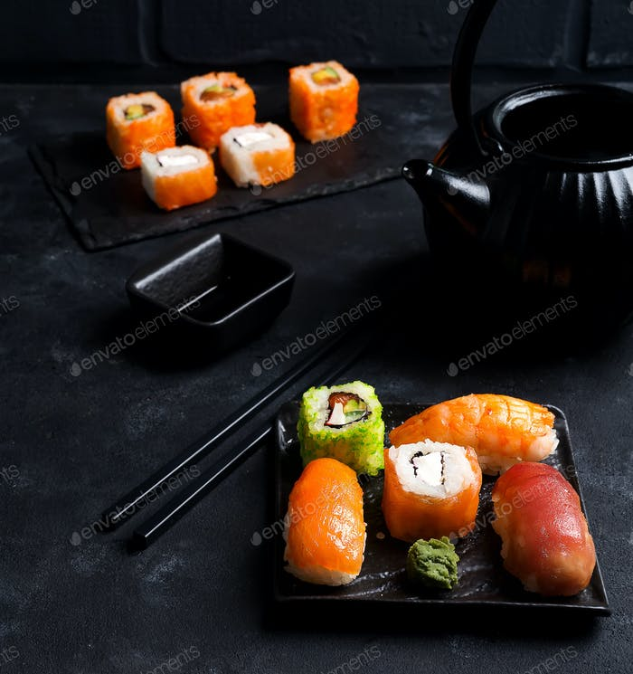 Asian food background with black iron teapot and sushi set on slate plate on black stone table