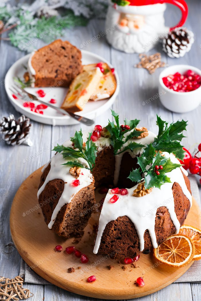 Christmas sliced chocolate cake with white icing, holly branches and pomegranate kernels on a gray