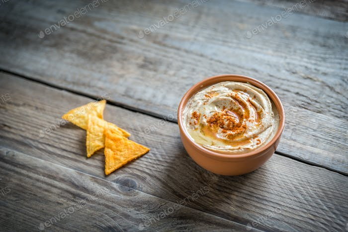Eine Schüssel Hummus mit Maischips