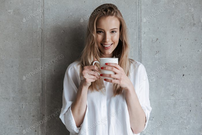 Woman indoors over grey wall drinking coffee holding cup.