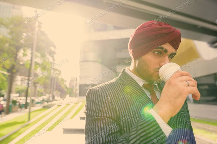 Young handsome Indian Sikh businessman wearing turban while exploring the city