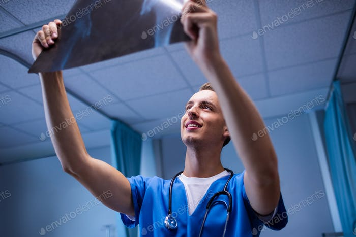Male doctor examining x-ray report