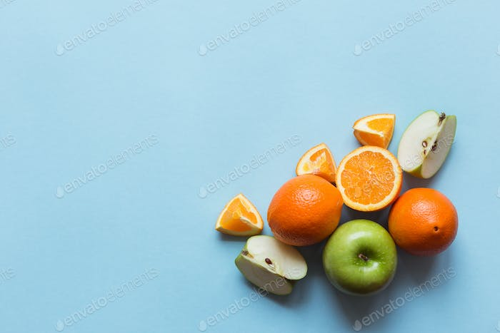 Fresh oranges and green apples on the blue background