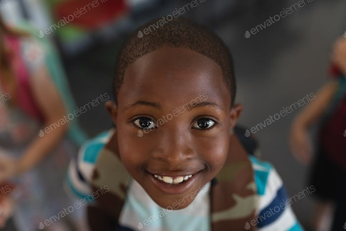 Close-up happy black schoolboy with schoolbag looking at camera in classroom of elementary school