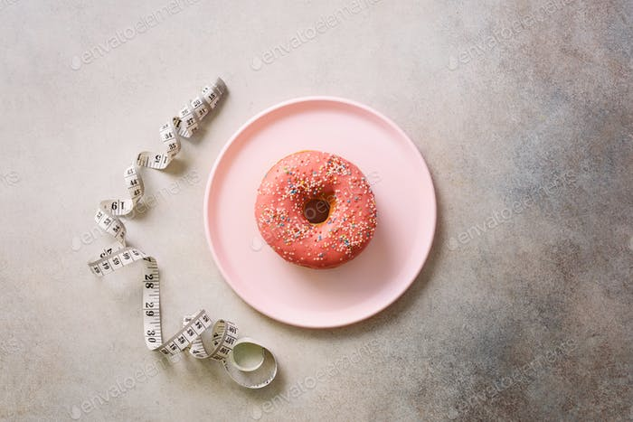Pink donut on plate, measuring tape over grey concrete background. Diet concept. Weight lost after