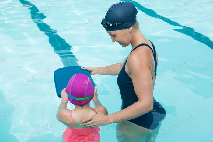 Female instructor training young girl in pool