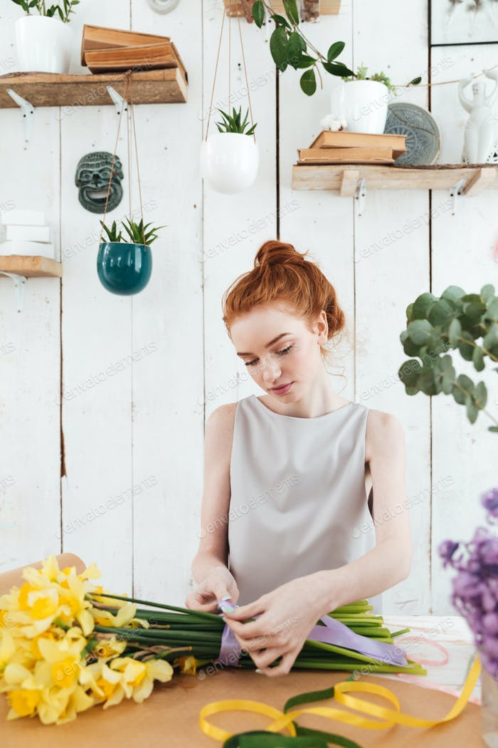 Serious concentrated woman making bouquet with ribbon in workshop