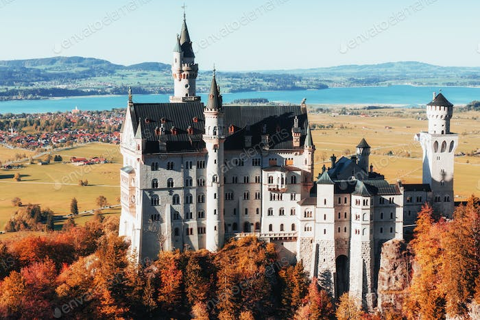 Neuschwanstein Castle standing on the plain with trees below and little town on background