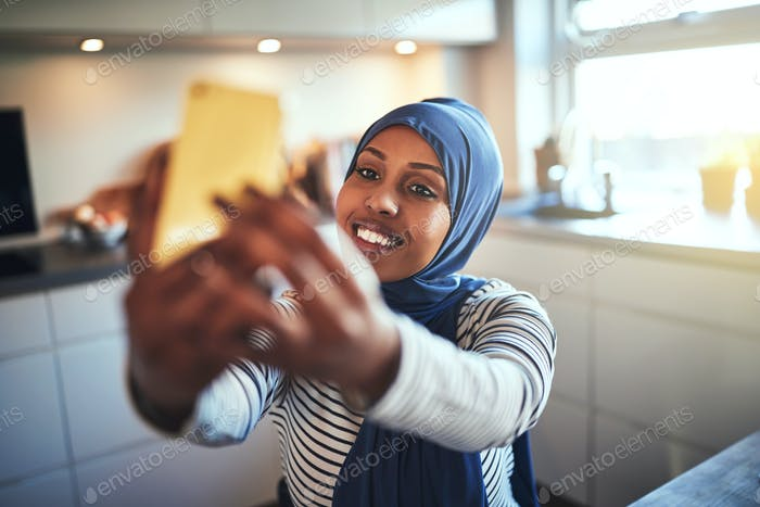 Lächelnd junge arabische Frau nehmen Selfies zu Hause