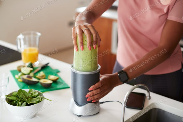 Close Up Of Woman Making Healthy Juice Drink With Fresh Ingredients In Electric Juicer