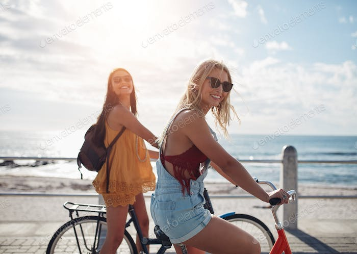 Two female friends riding their bicycles along seaside promenade