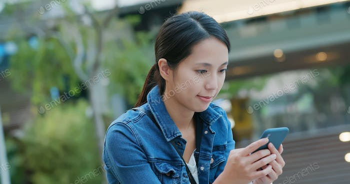 Woman look at mobile phone at outdoor