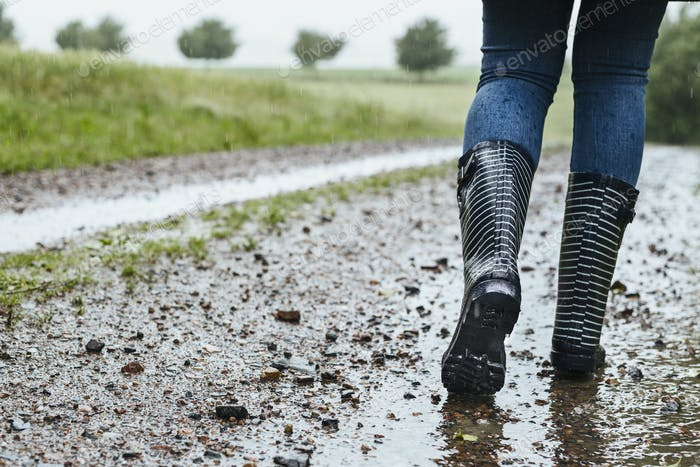 Low section of woman in wellington boots on dirt road