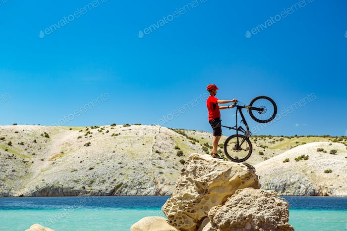 Mountain biker looking at mountains and beach