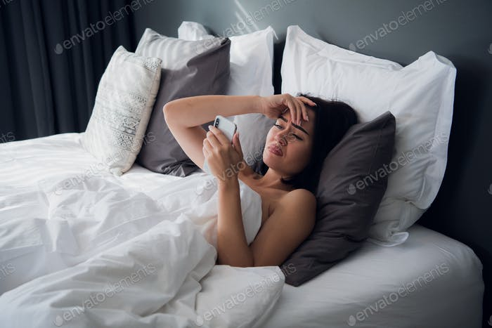 Image of frustrated upset woman 20s with dark hair lying in bed on white pillow after sleep and