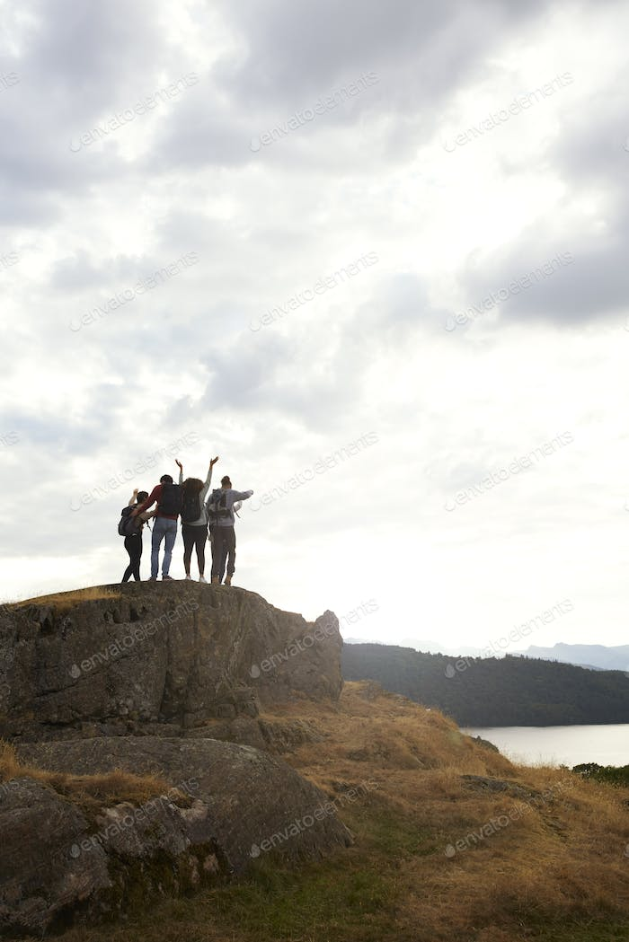 A silhouetted group of young adult friends celebrate arriving at the summit after a mountain hike