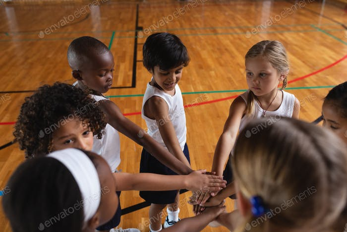 Overhead schoolkids forming hand stack at basketball court in school