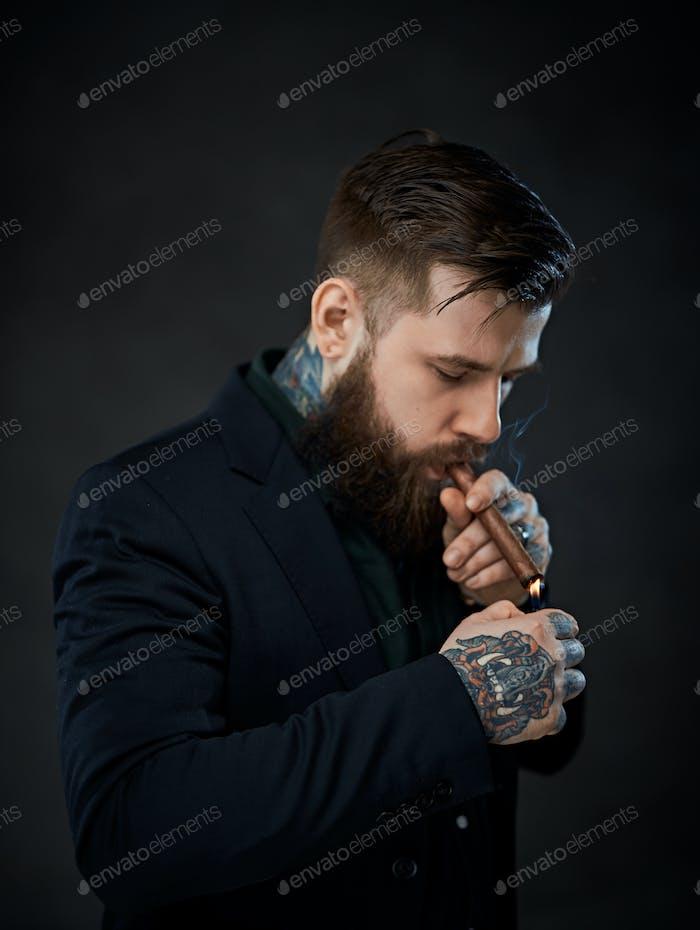Элегантно одетый бородатый мужчина с татуировками на шее и руке зажигает сигару