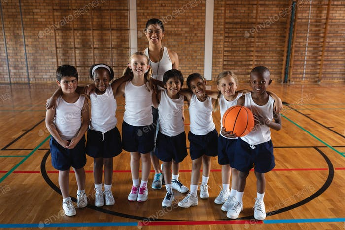 Front view of happy schoolkids and female coach looking at camera at basketball court in school