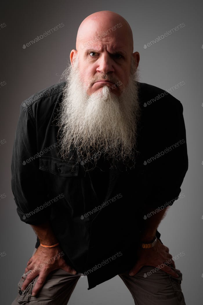 Stressed mature bald man with long beard looking angry while leaning forward