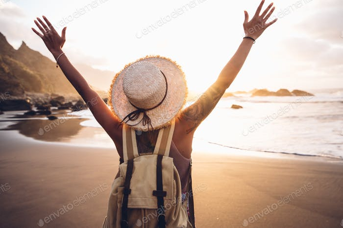 Woman walking on the beach enjoying sunset
