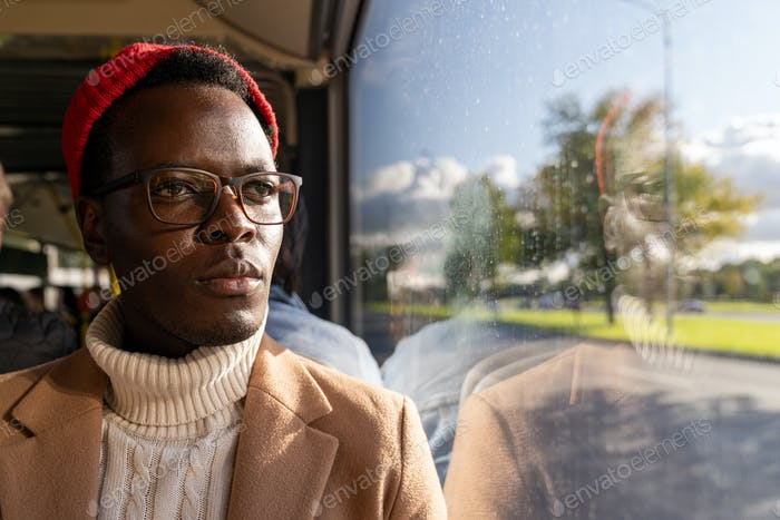 Pensive African young man wear glasses, looking at window, traveling by public transportation.
