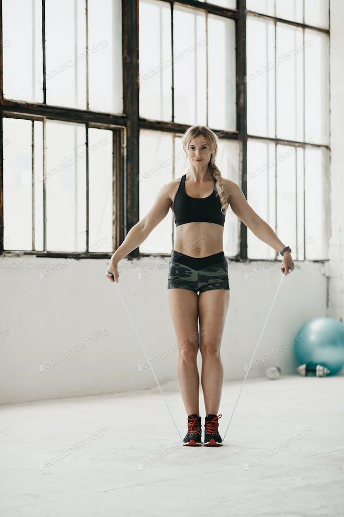 Cardio-Übung für den Körper. Schöne Frau in Sportbekleidung mit Fitness-Tracker springen mit Seil