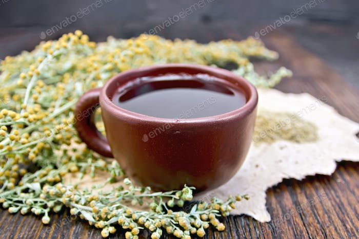Tea with wormwood in clay cup on board
