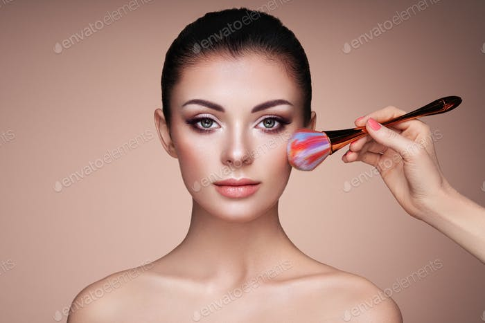 Beautiful Woman applies Skin Tone with Brush